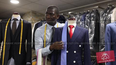Купить «Afro-american man seller is showing jacket and tie in shop», видеоролик № 32527370, снято 2 июля 2019 г. (c) Яков Филимонов / Фотобанк Лори