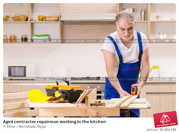 Aged contractor repairman working in the kitchen. Стоковое фото, фотограф Elnur / Фотобанк Лори