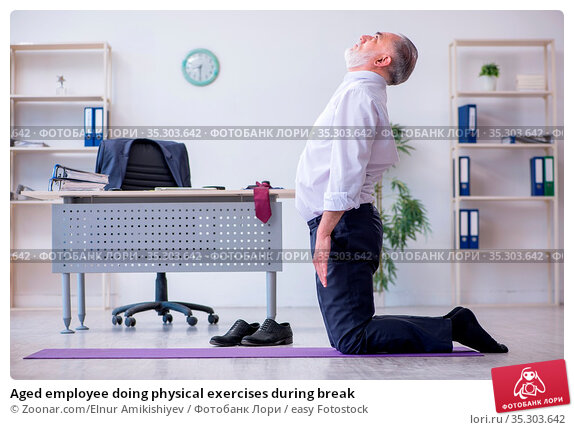Aged employee doing physical exercises during break. Стоковое фото, фотограф Zoonar.com/Elnur Amikishiyev / easy Fotostock / Фотобанк Лори