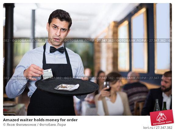 Купить «Amazed waiter holds money for order», фото № 27347382, снято 11 декабря 2017 г. (c) Яков Филимонов / Фотобанк Лори