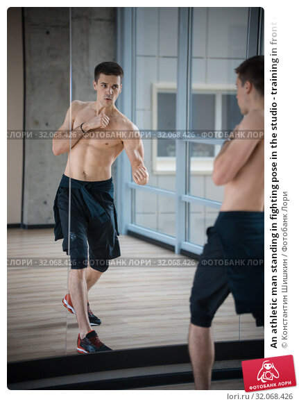 An athletic man standing in fighting pose in the studio - training in front of the mirror. Стоковое фото, фотограф Константин Шишкин / Фотобанк Лори