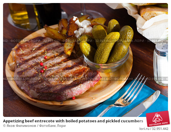 Appetizing beef entrecote with boiled potatoes and pickled cucumbers. Стоковое фото, фотограф Яков Филимонов / Фотобанк Лори