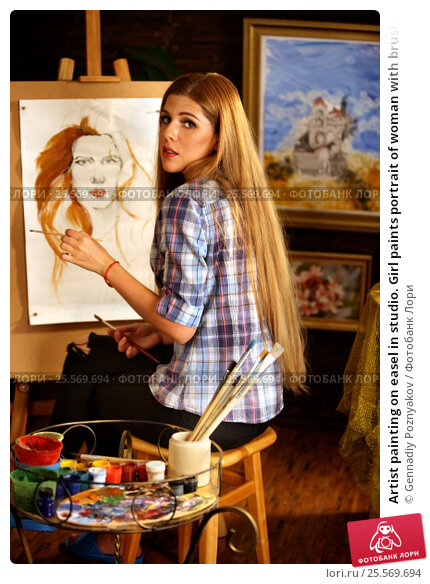 Artist painting on easel in studio. Girl paints portrait of woman with brush., фото № 25569694, снято 16 августа 2016 г. (c) Gennadiy Poznyakov / Фотобанк Лори