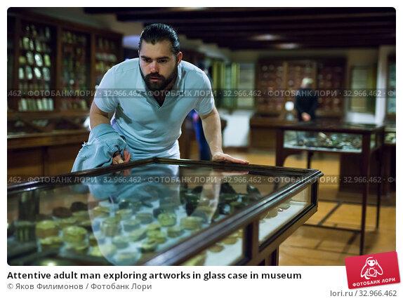 Купить «Attentive adult man exploring artworks in glass case in museum», фото № 32966462, снято 7 апреля 2019 г. (c) Яков Филимонов / Фотобанк Лори