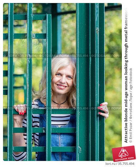 Attractive blonde mid-age woman looking through metal framework. Стоковое фото, фотограф Emil Pozar / age Fotostock / Фотобанк Лори