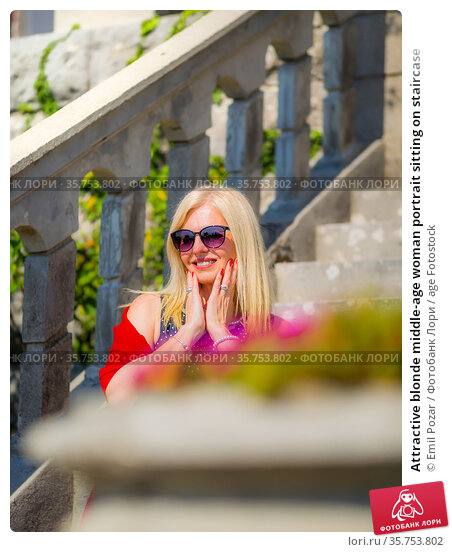 Attractive blonde middle-age woman portrait sitting on staircase. Стоковое фото, фотограф Emil Pozar / age Fotostock / Фотобанк Лори