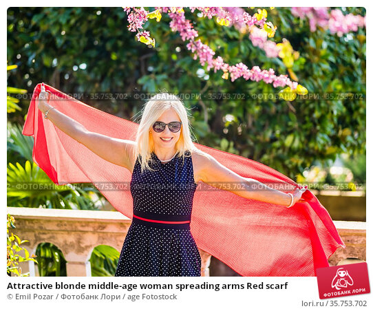 Attractive blonde middle-age woman spreading arms Red scarf. Стоковое фото, фотограф Emil Pozar / age Fotostock / Фотобанк Лори