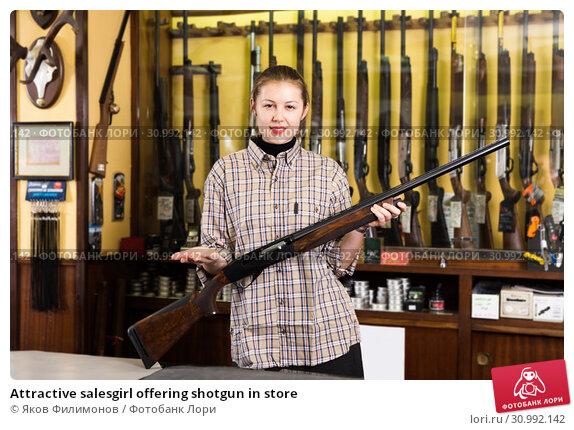 Купить «Attractive salesgirl offering shotgun in store», фото № 30992142, снято 11 декабря 2017 г. (c) Яков Филимонов / Фотобанк Лори