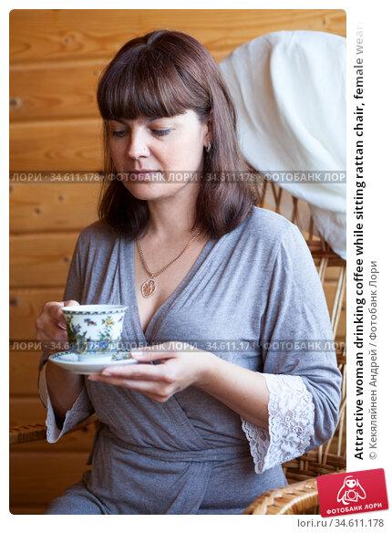 Attractive woman drinking coffee while sitting rattan chair, female wearing grey bathrobe. Стоковое фото, фотограф Кекяляйнен Андрей / Фотобанк Лори
