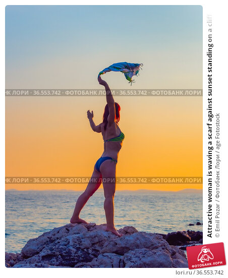 Attractive woman is waving a scarf against sunset standing on a cliff. Стоковое фото, фотограф Emil Pozar / age Fotostock / Фотобанк Лори