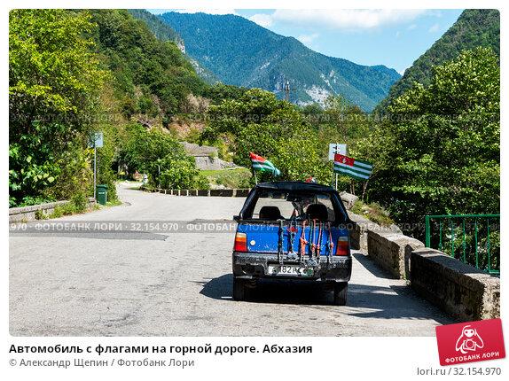 Купить «Автомобиль с флагами на горной дороге. Абхазия», эксклюзивное фото № 32154970, снято 11 сентября 2017 г. (c) Александр Щепин / Фотобанк Лори