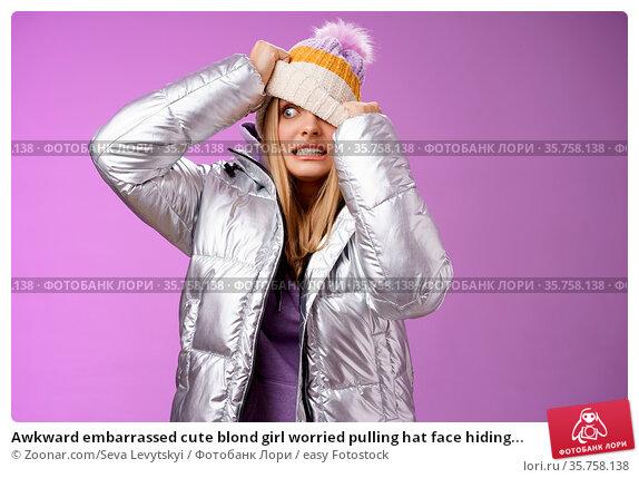 Awkward embarrassed cute blond girl worried pulling hat face hiding... Стоковое фото, фотограф Zoonar.com/Seva Levytskyi / easy Fotostock / Фотобанк Лори