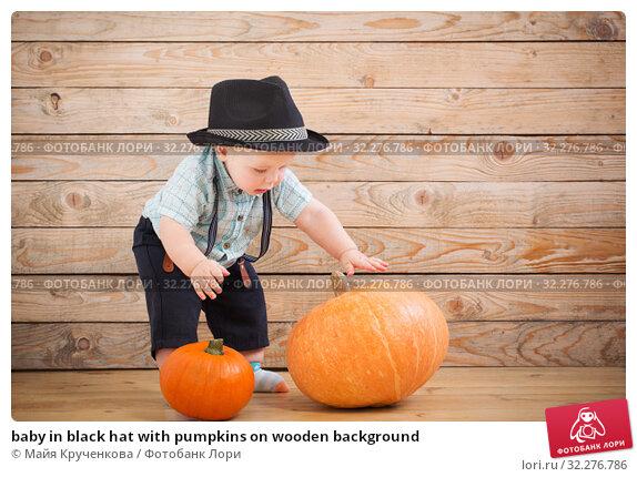 Купить «baby in black hat with pumpkins on wooden background», фото № 32276786, снято 7 октября 2019 г. (c) Майя Крученкова / Фотобанк Лори