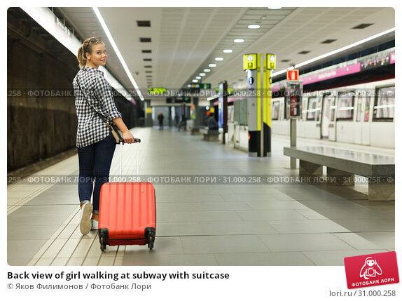 Купить «Back view of girl walking at subway with suitcase», фото № 31000258, снято 27 апреля 2018 г. (c) Яков Филимонов / Фотобанк Лори