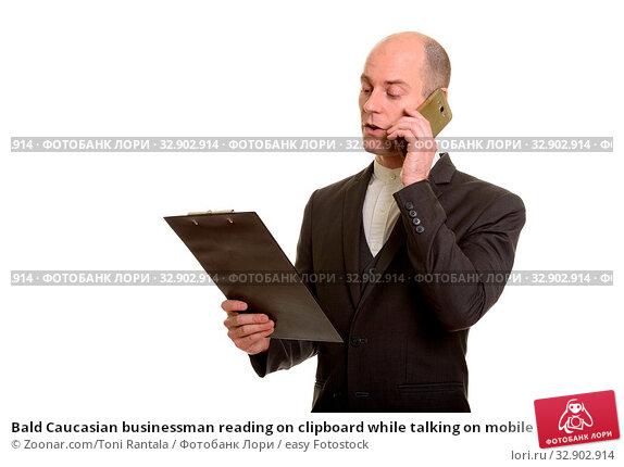 Bald Caucasian businessman reading on clipboard while talking on mobile phone. Стоковое фото, фотограф Zoonar.com/Toni Rantala / easy Fotostock / Фотобанк Лори