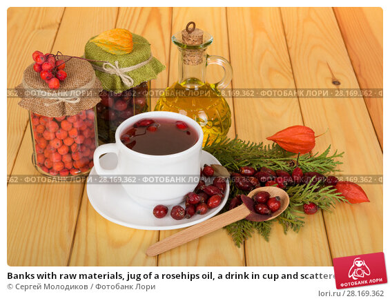 Купить «Banks with raw materials, jug of a rosehips oil, a drink in cup and scattered rosehip, on wooden table», фото № 28169362, снято 28 октября 2015 г. (c) Сергей Молодиков / Фотобанк Лори