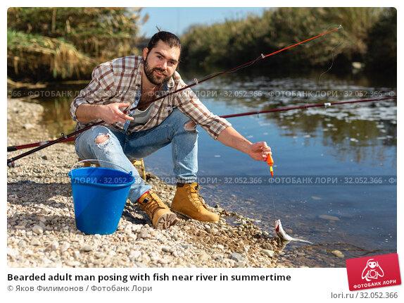 Bearded adult man posing with fish near river in summertime. Стоковое фото, фотограф Яков Филимонов / Фотобанк Лори