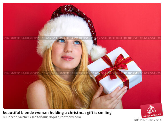 beautiful blonde woman holding a christmas gift is smiling. Стоковое фото, фотограф Doreen Salcher / PantherMedia / Фотобанк Лори