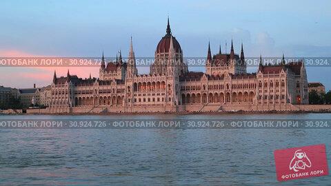 Купить «Beautiful evening view of the Hungarian Parliament Building and the Danube River at sunset in Budapest», видеоролик № 30924726, снято 3 июня 2019 г. (c) Яна Королёва / Фотобанк Лори
