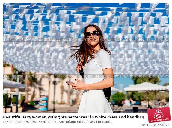 Beautiful sexy woman young brunette wear in white dress and handbag. Стоковое фото, фотограф Zoonar.com/Oleksii Hrecheniuk / easy Fotostock / Фотобанк Лори