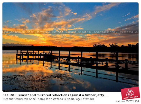 Beautiful sunset and mirrored reflections against a timber jetty ... Стоковое фото, фотограф Zoonar.com/Leah-Anne Thompson / age Fotostock / Фотобанк Лори