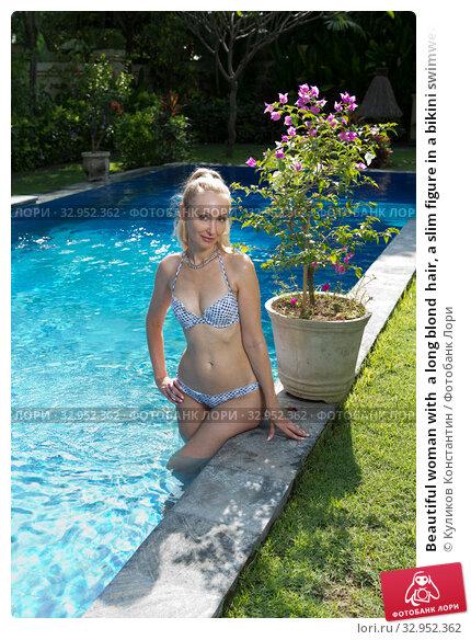 Beautiful woman with  a long blond  hair, a slim figure in a bikini swimwear in the pool with bright blue water in a tropical garden. Стоковое фото, фотограф Куликов Константин / Фотобанк Лори