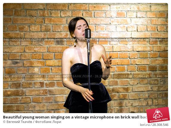 Купить «Beautiful young woman singing on a vintage microphone on brick wall background», фото № 28308546, снято 2 декабря 2017 г. (c) Евгений Ткачёв / Фотобанк Лори