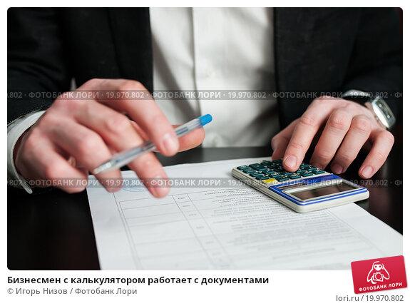 Бизнесмен с калькулятором работает с документами, эксклюзивное фото № 19970802, снято 10 января 2016 г. (c) Игорь Низов / Фотобанк Лори