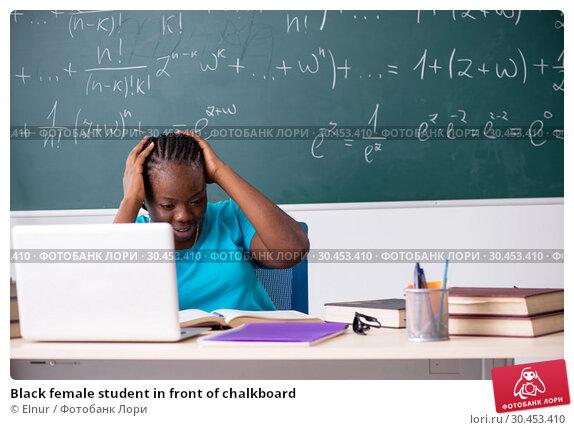 Black female student in front of chalkboard. Стоковое фото, фотограф Elnur / Фотобанк Лори