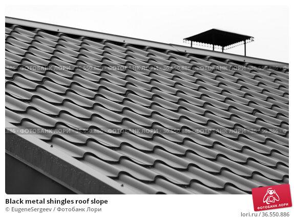 Black metal shingles roof slope. Стоковое фото, фотограф EugeneSergeev / Фотобанк Лори