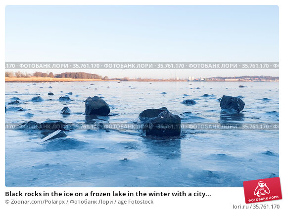 Black rocks in the ice on a frozen lake in the winter with a city... Стоковое фото, фотограф Zoonar.com/Polarpx / age Fotostock / Фотобанк Лори
