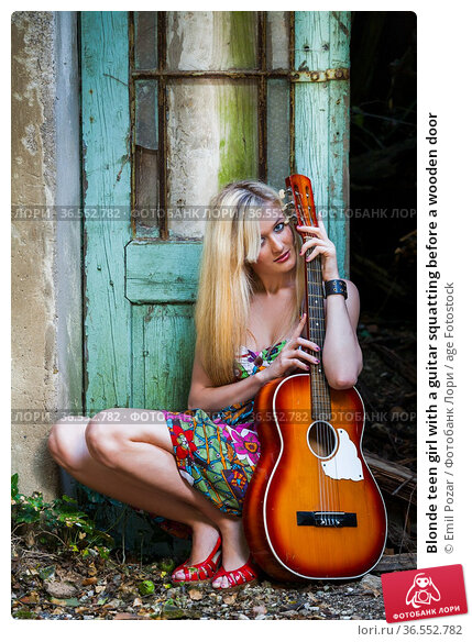Blonde teen girl with a guitar squatting before a wooden door. Стоковое фото, фотограф Emil Pozar / age Fotostock / Фотобанк Лори