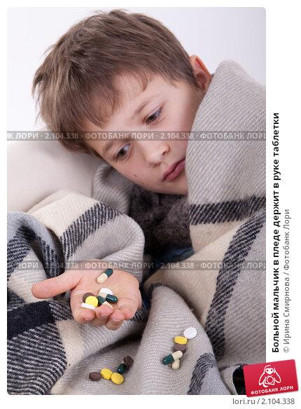 Купить «Больной мальчик в пледе держит в руке таблетки», фото № 2104338, снято 1 ноября 2010 г. (c) Ирина Смирнова / Фотобанк Лори