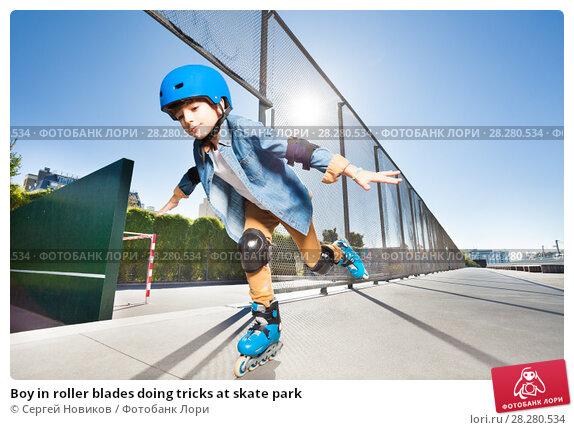 Купить «Boy in roller blades doing tricks at skate park», фото № 28280534, снято 14 октября 2017 г. (c) Сергей Новиков / Фотобанк Лори