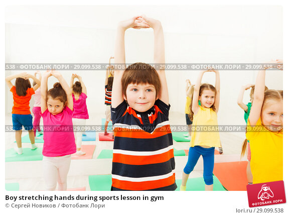 Купить «Boy stretching hands during sports lesson in gym», фото № 29099538, снято 15 апреля 2017 г. (c) Сергей Новиков / Фотобанк Лори