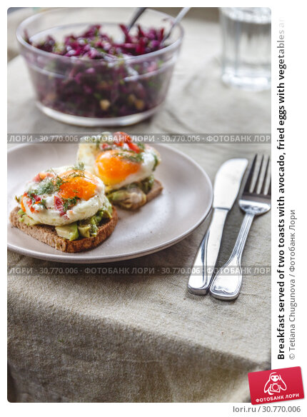 Купить «Breakfast served of two toasts with avocado, fried eggs with vegetables and herbs on a rustic tablecloth background. View from above. Healthy and nutritious food concept.», фото № 30770006, снято 11 декабря 2018 г. (c) Tetiana Chugunova / Фотобанк Лори