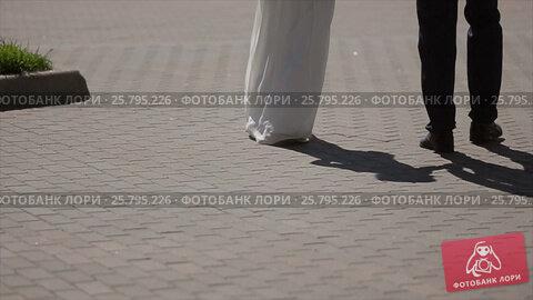 Bride and groom walking on a street, видеоролик № 25795226, снято 16 марта 2016 г. (c) Алексей Макаров / Фотобанк Лори