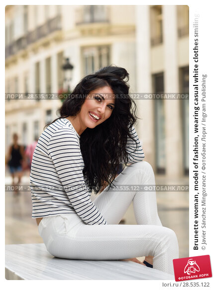 Купить «Brunette woman, model of fashion, wearing casual white clothes smiling in the street. Young girl with curly hairstyle sitting in urban background.», фото № 28535122, снято 7 июля 2016 г. (c) Ingram Publishing / Фотобанк Лори