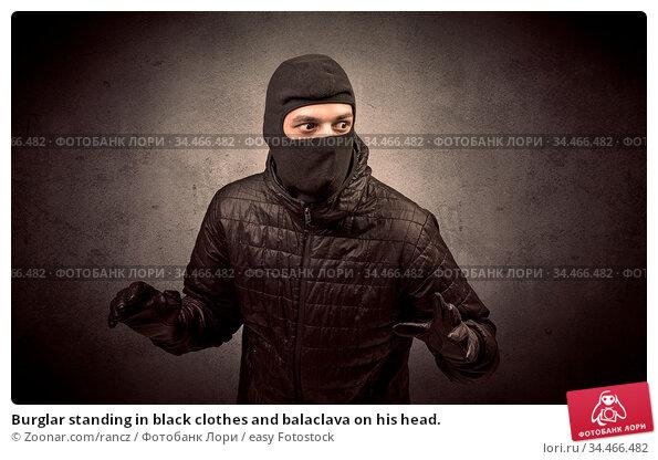 Burglar standing in black clothes and balaclava on his head. Стоковое фото, фотограф Zoonar.com/rancz / easy Fotostock / Фотобанк Лори