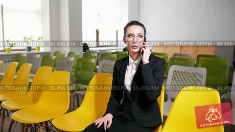 Business concept. A woman sits in the business centre and talking on her phone. Стоковое видео, видеограф Константин Шишкин / Фотобанк Лори