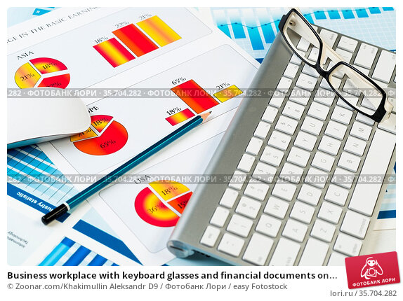 Business workplace with keyboard glasses and financial documents on... Стоковое фото, фотограф Zoonar.com/Khakimullin Aleksandr D9 / easy Fotostock / Фотобанк Лори