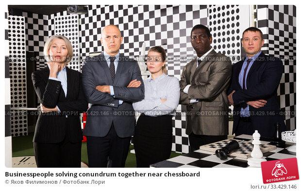 Купить «Businesspeople solving conundrum together near chessboard», фото № 33429146, снято 29 января 2019 г. (c) Яков Филимонов / Фотобанк Лори