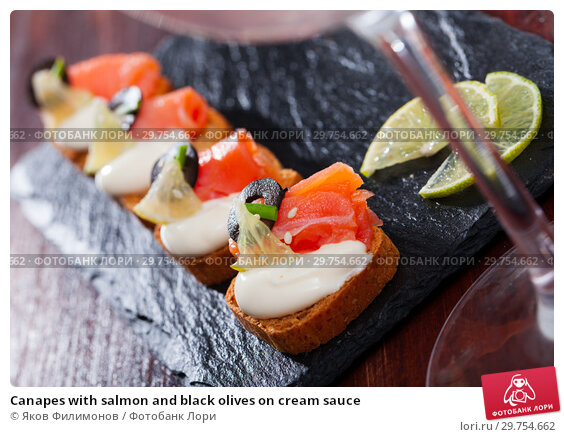 Купить «Canapes with salmon and black olives on cream sauce», фото № 29754662, снято 19 февраля 2019 г. (c) Яков Филимонов / Фотобанк Лори