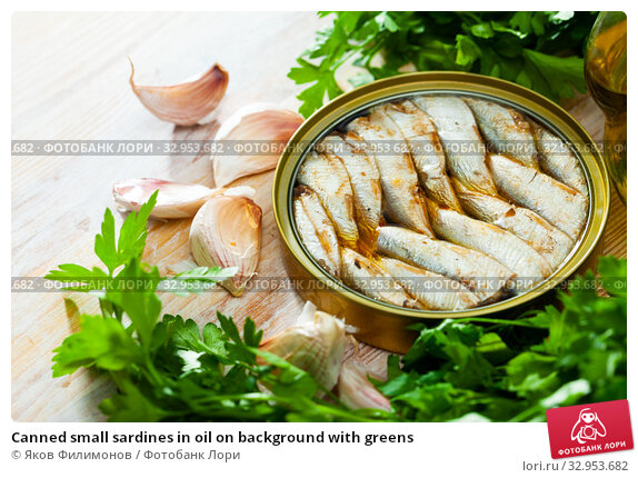 Canned small sardines in oil on background with greens. Стоковое фото, фотограф Яков Филимонов / Фотобанк Лори