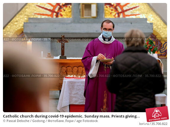 Catholic church during covid-19 epidemic. Sunday mass. Priests giving... Стоковое фото, фотограф Pascal Deloche / Godong / age Fotostock / Фотобанк Лори