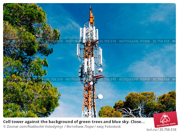Cell tower against the background of green trees and blue sky. Close... Стоковое фото, фотограф Zoonar.com/Nadtochii Volodymyr / easy Fotostock / Фотобанк Лори