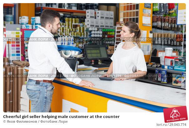 Купить «Cheerful girl seller helping male customer at the counter», фото № 29043774, снято 17 мая 2018 г. (c) Яков Филимонов / Фотобанк Лори
