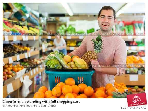 Купить «Cheerful man standing with full shopping cart», фото № 30917154, снято 27 апреля 2019 г. (c) Яков Филимонов / Фотобанк Лори