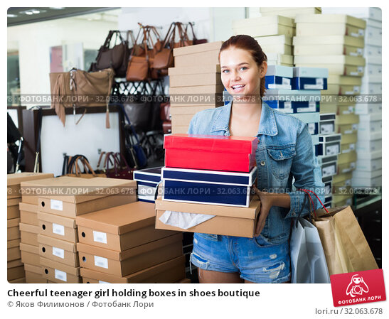 Cheerful teenager girl holding boxes in shoes boutique. Стоковое фото, фотограф Яков Филимонов / Фотобанк Лори