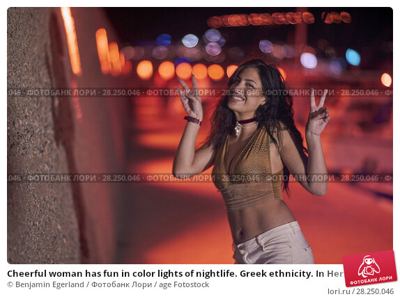 Купить «Cheerful woman has fun in color lights of nightlife. Greek ethnicity. In Hersonissos, Crete, Greece», фото № 28250046, снято 16 сентября 2017 г. (c) age Fotostock / Фотобанк Лори